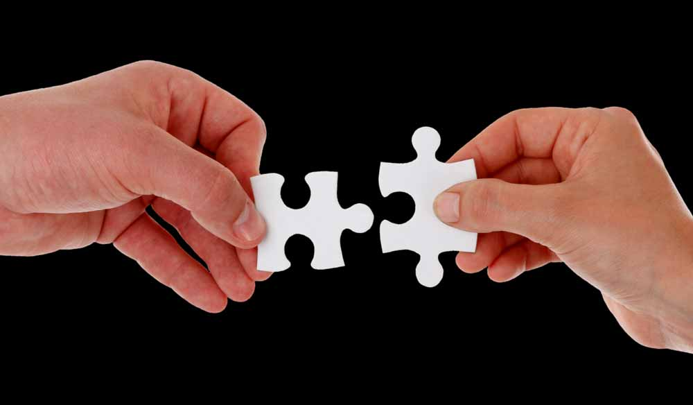 Two hands holding out pieces of a puzzle that fit together, represents Conscious Marketing working with you to create a marketing strategy suited to your needs.