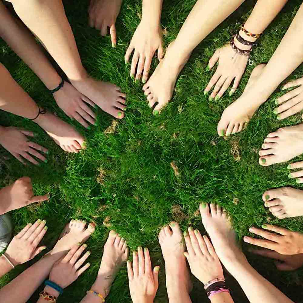 Hands and feet in a circle on a patch of grass representing the sense of community that happens when you build trust with your clients.