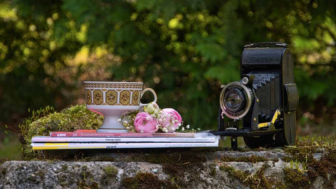 On a stone wall a small pile of magazies with a teacup and flowers sitting on top, and an old style camera sitting beside, represents the focus and attention to detail and the scope of marketing provided incorporaing magazines and newsletters.