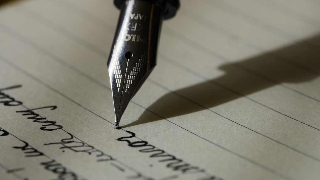 A calligraphy pen writing on a notepad
